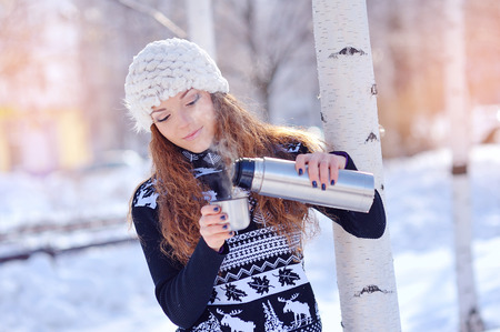 forest tea: Girl drinking hot tea in the winter forest. Stock Photo