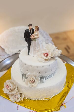 wedding table decor: traditional and decorative wedding cake at wedding reception.