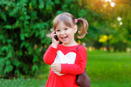 speaks: child speaks on the phone in the park. Stock Photo