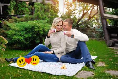 picknick: Happy couple in nature drinking tea outdoors having picnic in fall season smiling laughing