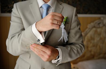 groom wears cufflinks