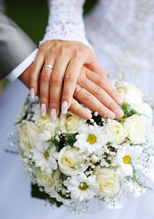 Hands of the groom and the bride with wedding rings and a wedding bouquet from roses.