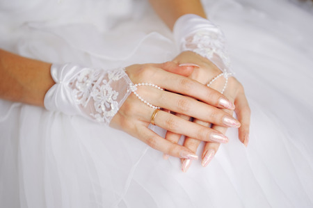Elegant brides hands with golden ring.