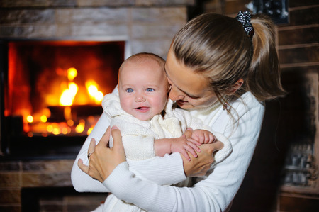 burning fireplace: mother kisses daughter at the burning fireplace.