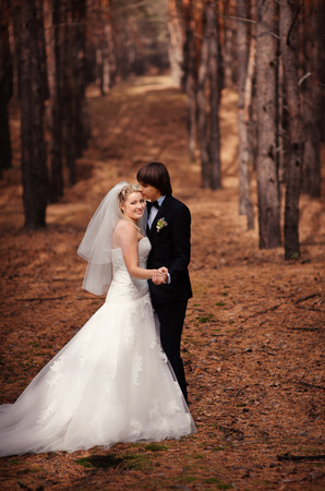 Happy bride and groom walking in the autumn forest. Stock Photo