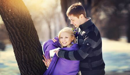 warms: Loving couple in winter, boy care warms Woman scarf.