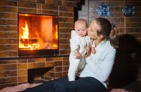 woodburner: Mother kisses daughter at the fireplace. Stock Photo