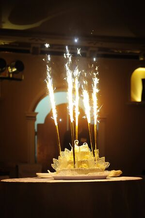sugarpaste: Celebration! Flaming Wedding Cake against black .