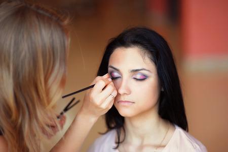 beautician: beautician applying makeup. Stock Photo