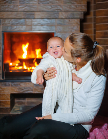 woodburner: Mother and daughter sitting by a fireplace in their family home on Christmas eve.
