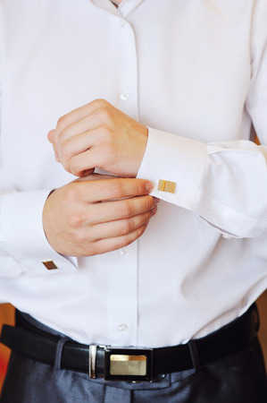 suit  cuff: Man puts cuff links on sleeve white shirts. Stock Photo