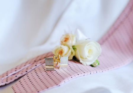 cuff link: Wedding rings, cufflinks tie on the couch.
