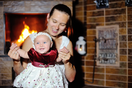 baby open present: Daughter with her mother at the fireplace.
