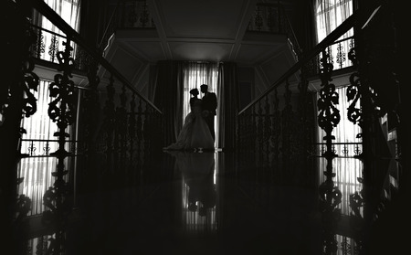 nighttime: silhouette of the bride and groom at a wedding.
