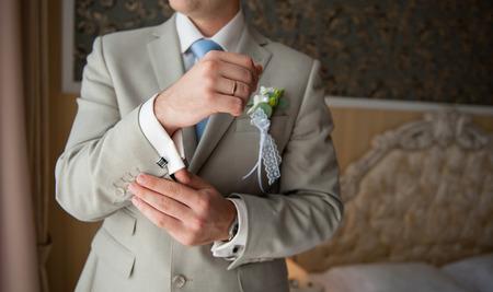 terno: el novio en un traje, manos desgaste gemelos. Foto de archivo