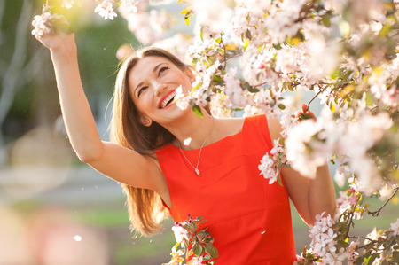 Beautiful smiling woman with spring flowers . Foto de archivo