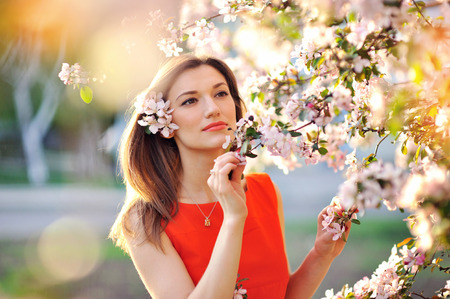 Sensual portrait of a spring woman, beautiful face female enjoying cherry blossom, dreamy girl with pink fresh flowers outdoor, seasonal nature, tree branch and glamorous lady.