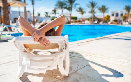 Beautiful young woman with flower in hair relaxing on sun lounger near pool. Archivio Fotografico