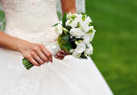 anillos de matrimonio: ramo de la boda blanca en manos de la novia. Foto de archivo