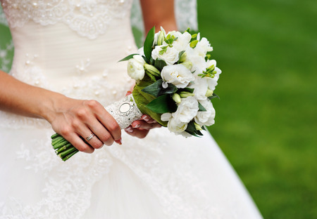 girl with rings: white wedding bouquet in hands of the bride.