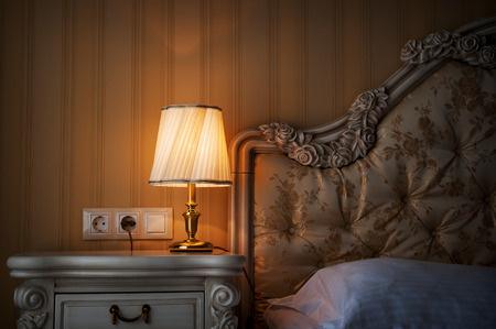 Lamp on a night table next to a bed. Standard-Bild