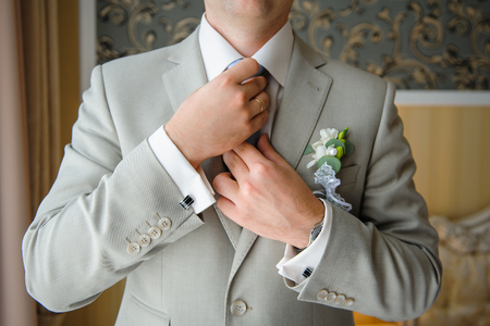 cuff link: man in a suit straightens his tie with cufflinks on their sleeves.