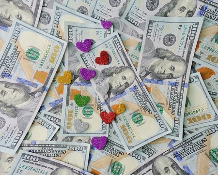 avarice: Hearts lie on money dollars, concept of love for money. Stock Photo