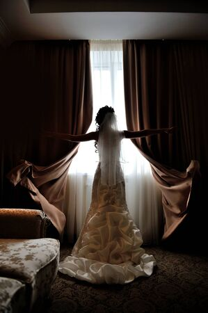 silhouette of the bride standing at the window of their wedding day. Foto de archivo