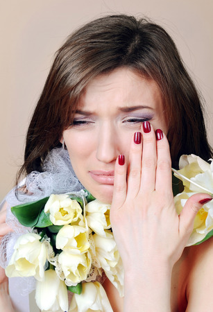 crying woman with white flowers tulips. Stock Photo