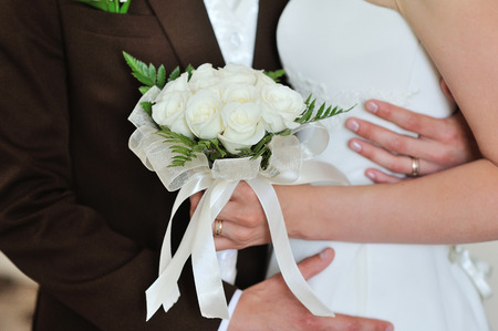 white wedding bouquet of roses in hands of the bride and groom. Archivio Fotografico
