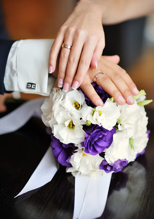 hands of the bride and groom with wedding rings on a background of the bouquet.