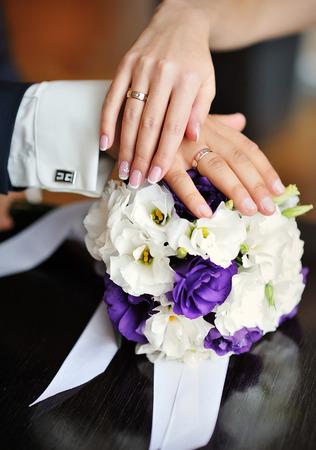 신부와 신랑의 손을 꽃다발의 배경에 결혼 반지와 함께.