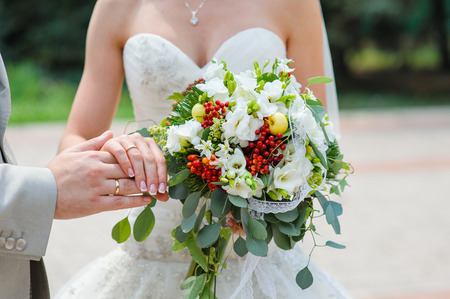groom and bride: hands with rings bride and groom with wedding bouquet.