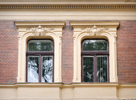 heads old building facade: beautiful baroque architectural window.