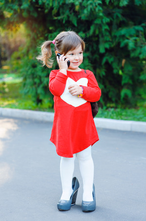 big shoes: little girl in big shoes talking on the phone. Stock Photo