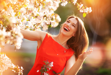 happy woman in spring flowering trees.