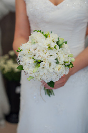 Bride holding a beautiful wedding bouquet of white flowers. Stock Photo
