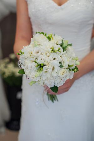 Bride holding a beautiful wedding bouquet of white flowers. Foto de archivo