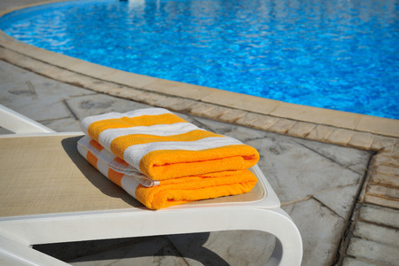 Two yellow striped towels lie on a sun-bed near a swimming pool.