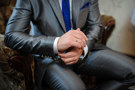 cufflinks: man in a suit sitting in a chair and puts cufflinks.
