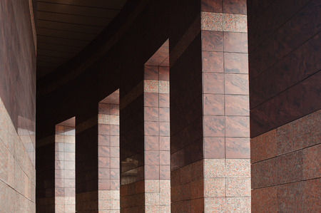 building sector: Row of columns with sunlight in the gaps and reflected in shiny floor.
