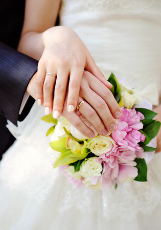 Hand of the groom and the bride on wedding bouquet.