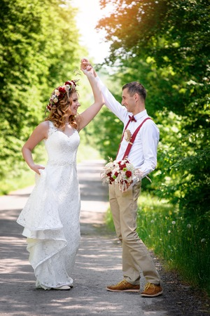 out of town: bride and groom walking on the road out of town Stock Photo