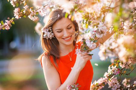 Beautiful woman in the flowering spring garden.
