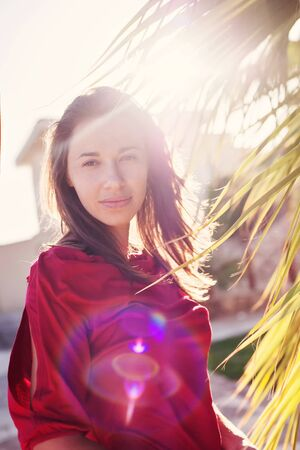 temptress: Beautiful girl near the palm trees and sun backlit.