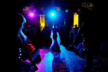 Silhouette of of bride dancing on the dance floor.