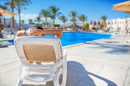 descansando: mujer tendida en una tumbona junto a la piscina en el hotel.