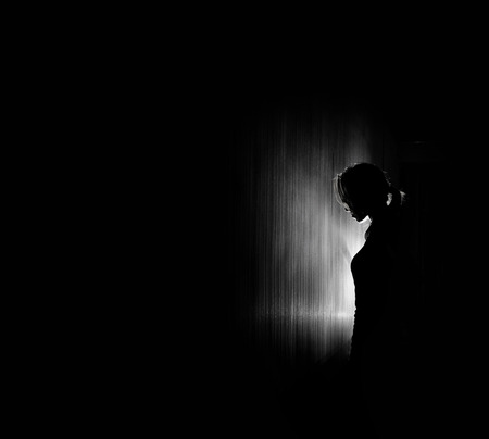 anxiety: beautiful woman silhouette, black background.