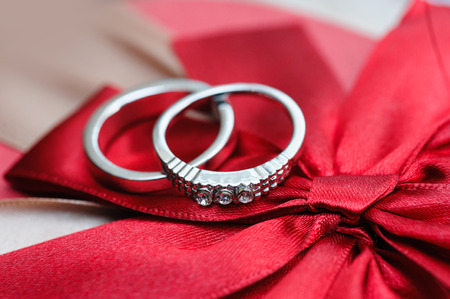 anillos de matrimonio: dos anillos de boda en fondo rojo. Foto de archivo