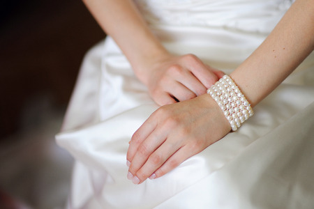 bride bangle: White bracelet on a hand of the bride in a white dress Stock Photo